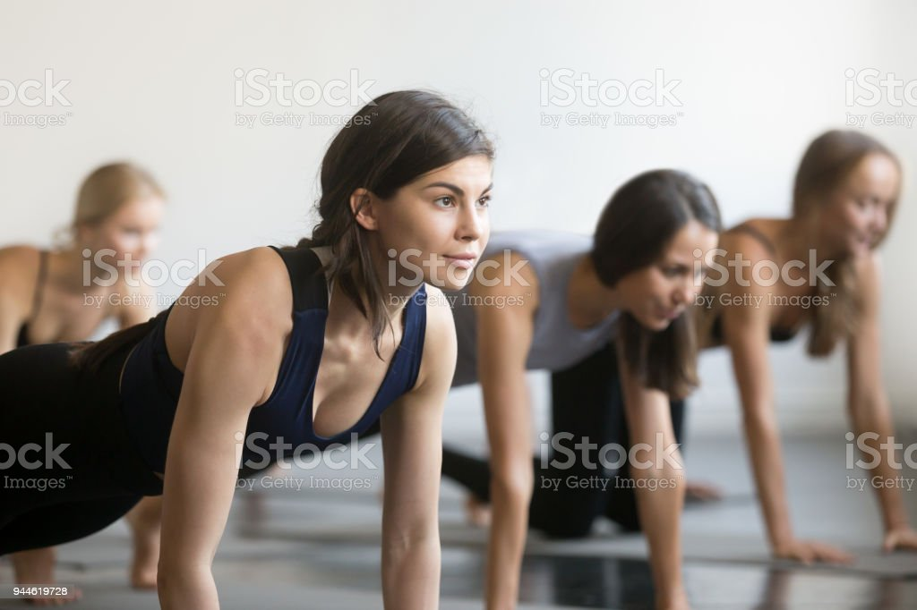 Group of young sporty people in Plank pose, close up stock photo
