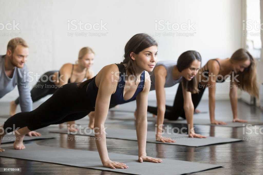 Group of young sporty people in Plank pose stock photo