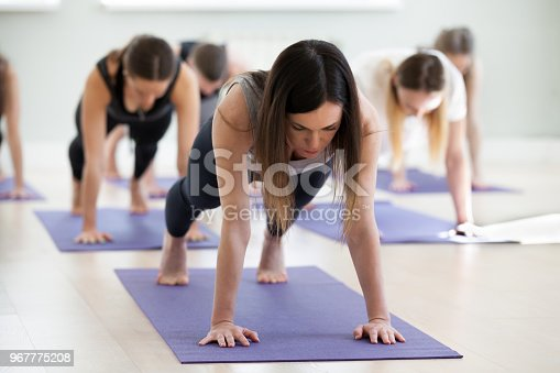 914755448istockphoto Group of young sporty people in Plank pose 967775208