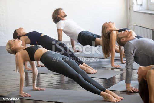 914755448istockphoto Group of young sporty people in Purvottanasana pose 846236668