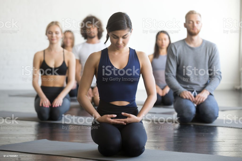 Group of young sporty people in vajrasana pose stock photo