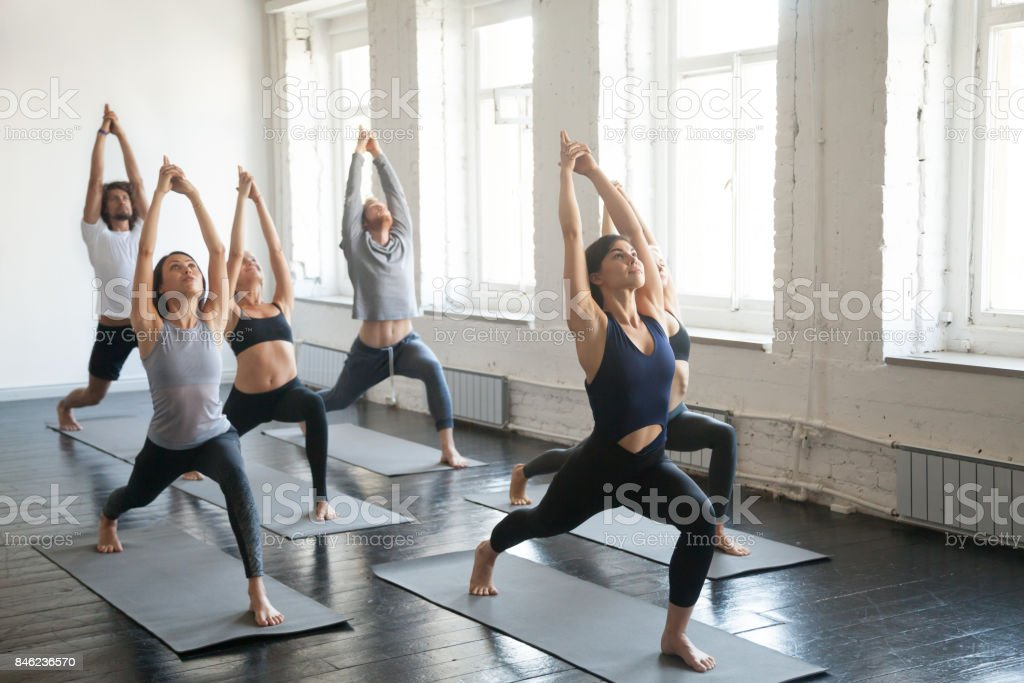 Group of young sporty people in Warrior one pose, studio stock photo