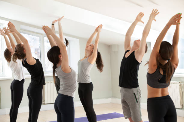 Group of young sporty people Group of young sporty people practicing yoga lesson, doing Tadasana exercise, mountain pose, working out, indoor close up, yogi students training in sport club. Wellness, wellbeing concept sun salutation stock pictures, royalty-free photos & images
