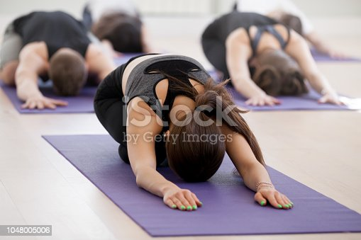 istock Group of young sporty people practicing yoga lesson, Child exercise 1048005006