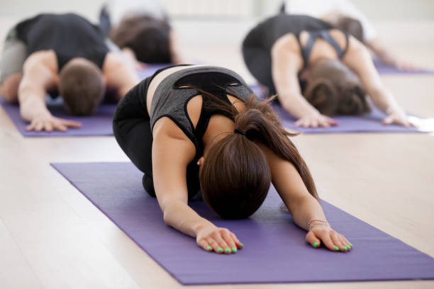 group of young sporty people practicing yoga lesson, child exercise - yin yang symbol stock pictures, royalty-free photos & images