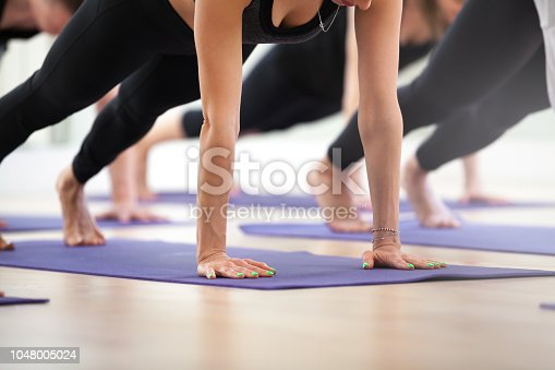 914755448istockphoto Group of young sporty people practicing yoga, Plank pose 1048005024