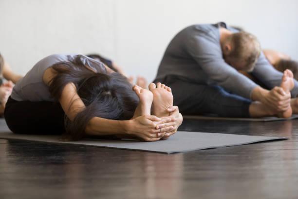 gruppe von jugendlichen sportliche sitzende nach vorne beugen - yin yoga stock-fotos und bilder
