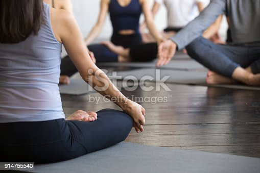 istock Group of young sporty people sitting in Lotus pose, closeup 914755540