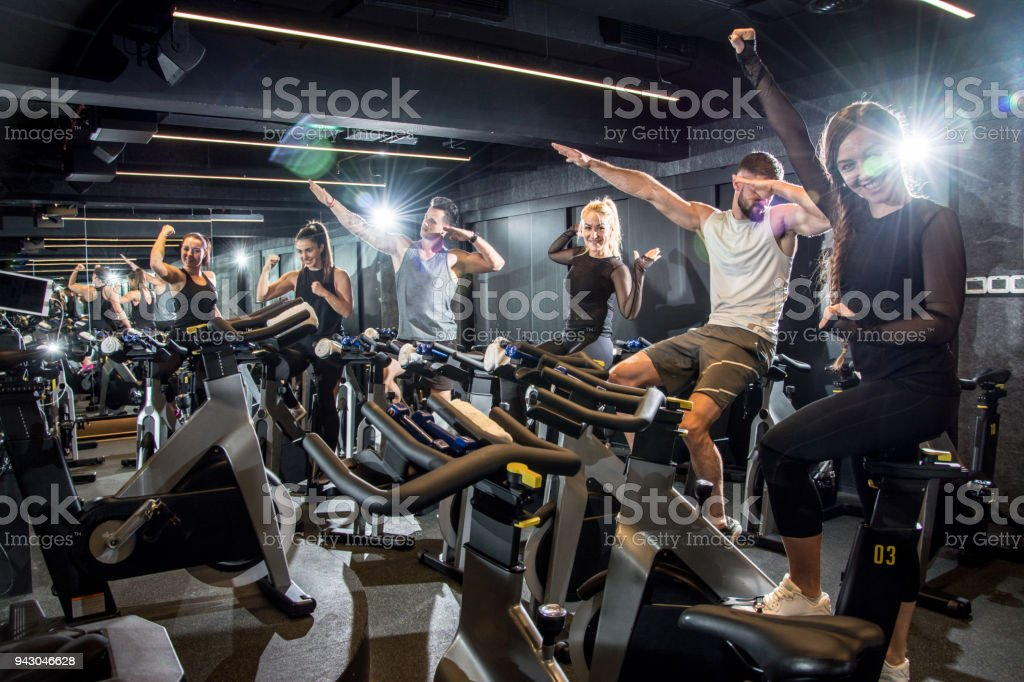 Group of young sporty people sitting on cycling bikes and having a break. Friends laughing with joy, feeling excited about training in gym stock photo