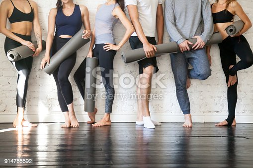 istock Group of young sporty people standing at wall, close up 914755592