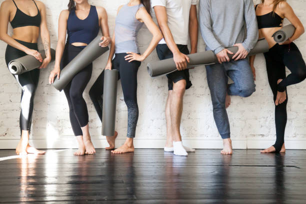 group of young sporty people standing at wall, close up - yoga stock photos and pictures
