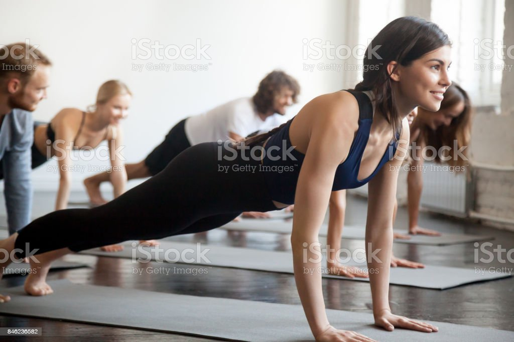 Group of young sporty smiling people in Plank pose stock photo