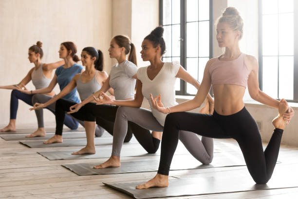 Group of young sporty women practicing yoga, doing Horse rider Group of young diverse sporty people doing yoga Horse rider exercise, anjaneyasana pose, working out indoor, mixed race female students training at club or studio. Well being, wellness concept sun salutation stock pictures, royalty-free photos & images