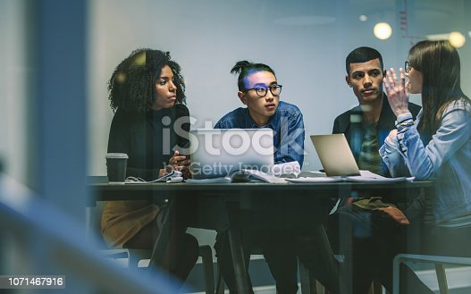 Woman talking with classmates while studying together around table. Young people sitting at the table working on an assignment.