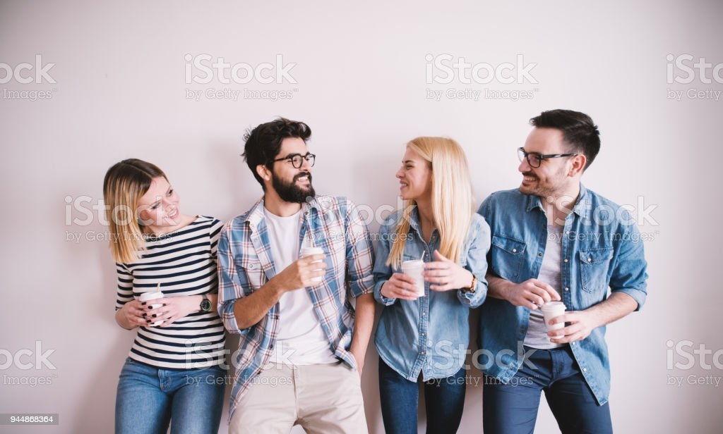 Group of young stylish happy people leaning against the wall and talking while drinks coffee in the paper cup. stock photo