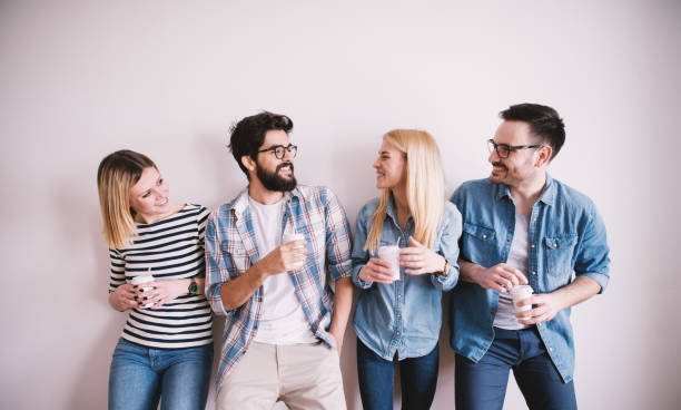 group of young stylish happy people leaning against the wall and talking while drinks coffee in the paper cup. - four people stock photos and pictures
