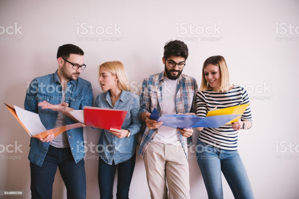 Group Of Young Stylish People Leaning Against The Wall And