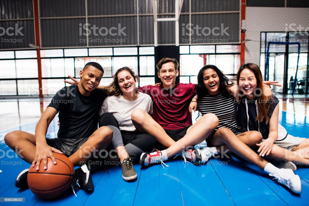 Group of young teenager friends on a basketball court relaxing portrait stock photo