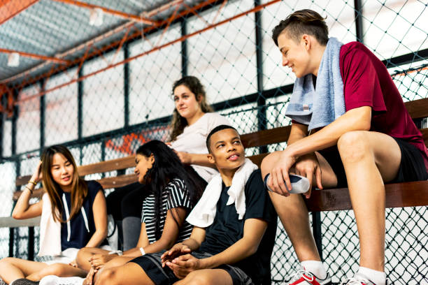 group of young teenager friends sitting on a bench relaxing - high school sports stock pictures, royalty-free photos & images