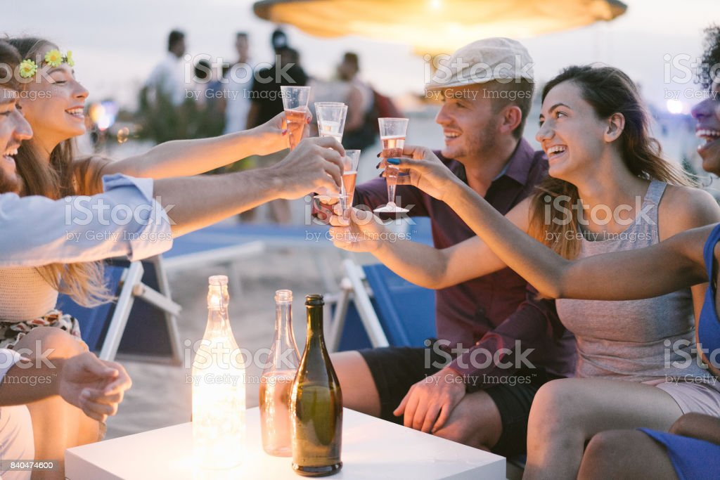 Group of young tourist friends cheering with champagne at beach kiosk party - Happy people having fun in summer holidays - Focus on girls hands glasses - Fun,vacation, hanging out and youth concept stock photo