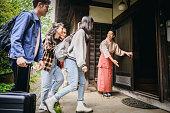日本の伝統的旅館に到着する若い旅行者のグループ