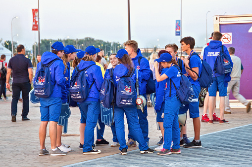 Group of young volunteers near modern Kaliningrad football stadium (also known as Arena Baltika) for holding games of the FIFA World Cup of 2018 in Russia.