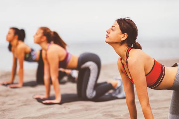 Gruppe junger Frau erwärmt sich vor Joggen am Strand am Meer – Foto