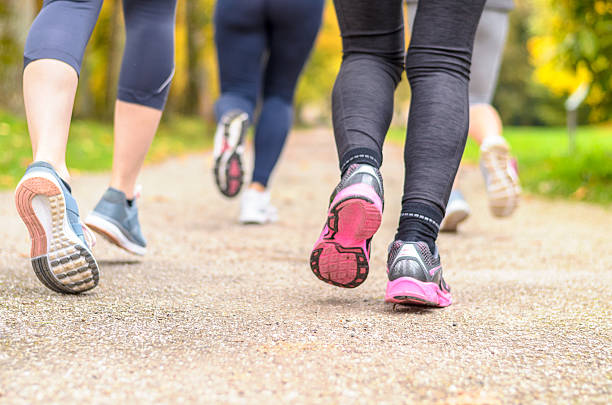 Group of young woman jogging together in a park stock photo