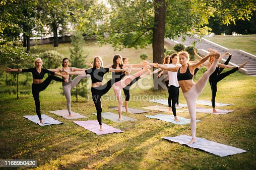 Group of young women are doing yoga exercise Utthita Hasta Padangusthasana. Group of women doing yoga extended hand-to-big-toe position standing on one leg and keeping balance in city park.
