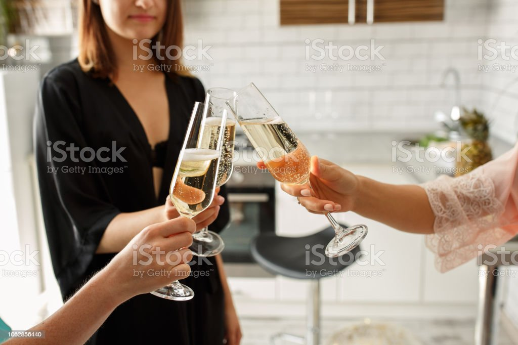 Group of young women cheering with champagne, celebrating bridal shower at home stock photo