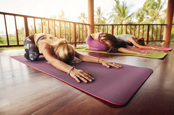 Group of young women doing child pose yoga Group of young women doing stretching workout on fitness mat. Women at yoga class bending forward on their yoga mats. Fitness people doing child pose, Balasana. childs pose stock pictures, royalty-free photos & images