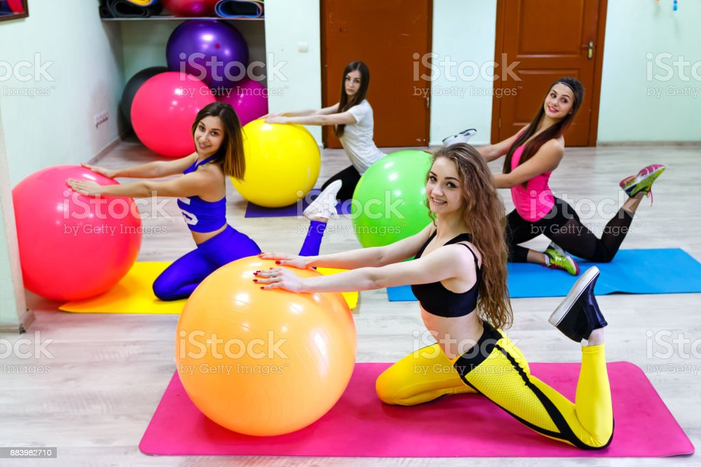 group of young women doing exercises with fitballs in a fitnes stock photo