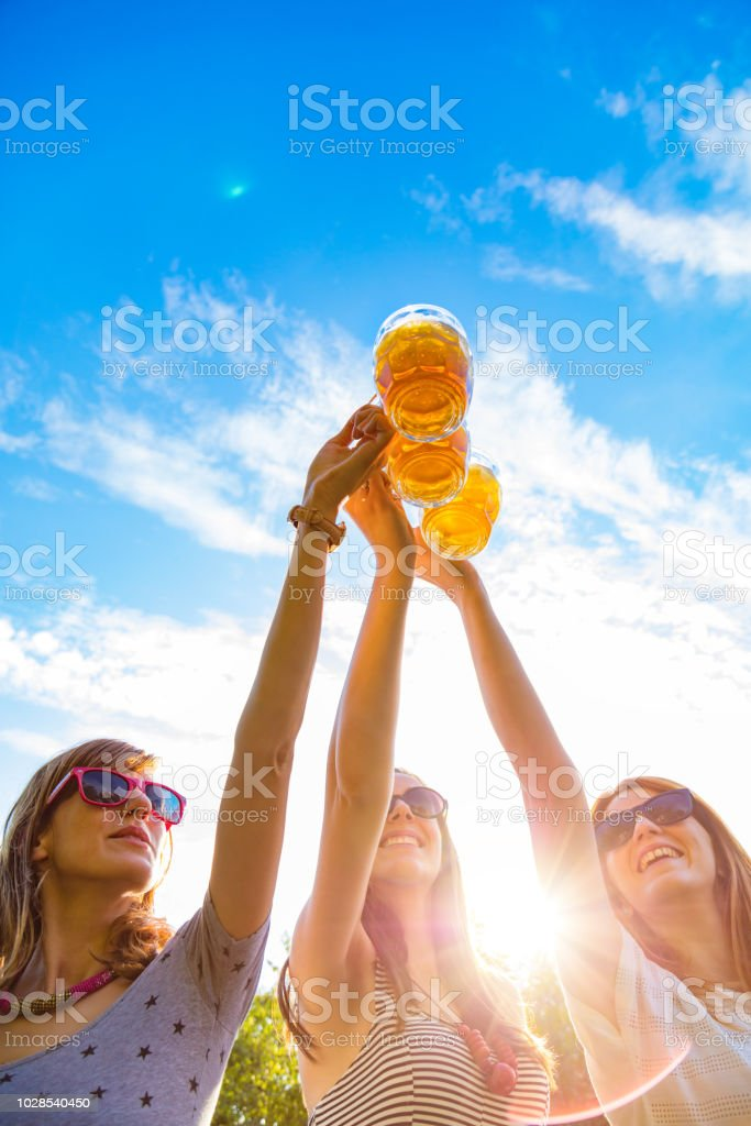 Group of young women enjoying outdoors with beer. stock photo