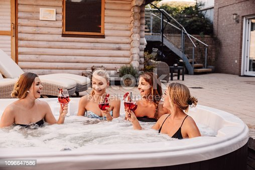 Group of young women having fun in hot tub whirlpool outdoors  Bachelorette ladies night with women pool and drinks Photo taken outdoors in natural sunlight in summer