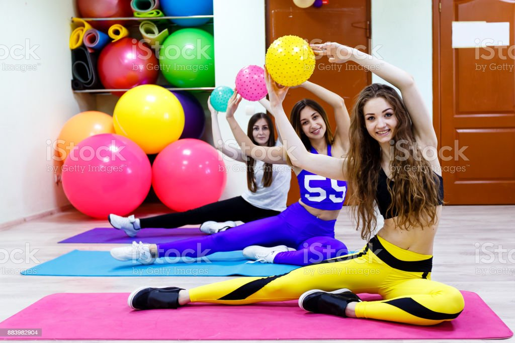 Group of young women holding balls  sitting on a floor in fitnes stock photo