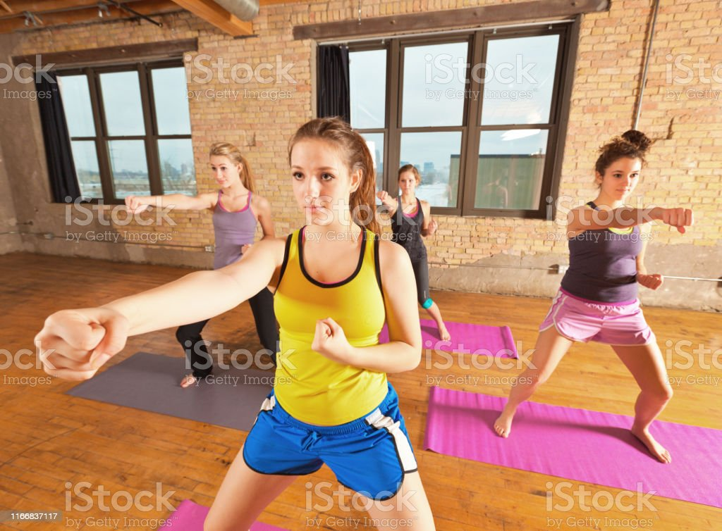 Four young women in a aerobic kung fu exercise health group...