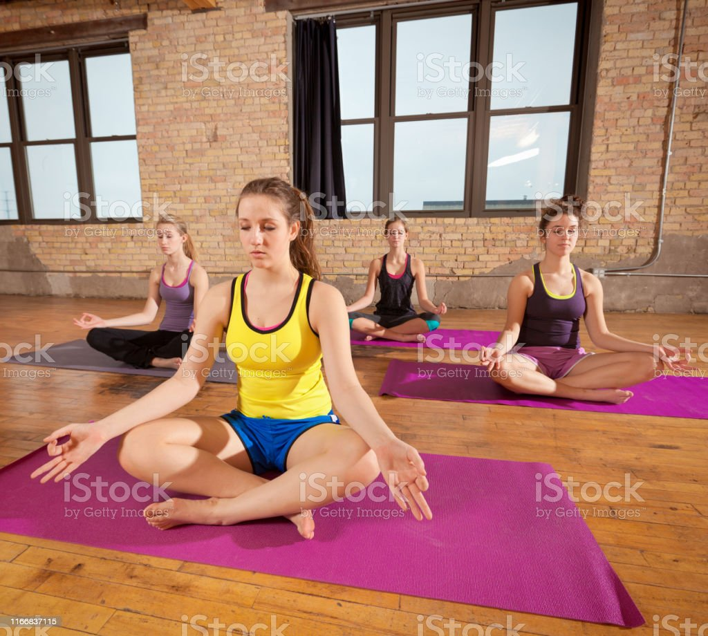 Four young women in a yoga exercise health group practicing yoga...