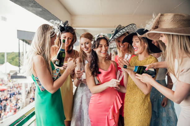 group of young women opening a bottle of champagne - horse racing стоковые фото и изображения