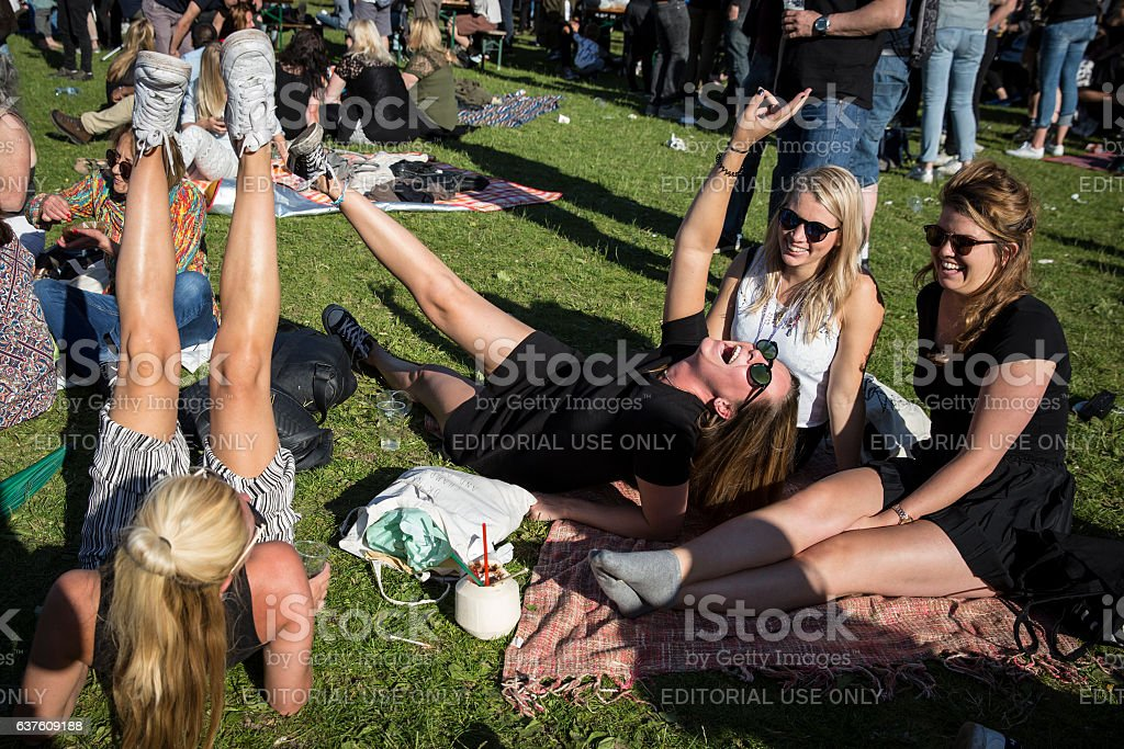 group of young women sitting on the grass and laughing stock photo