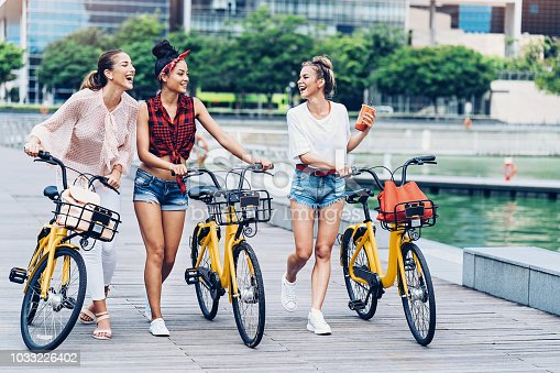 Group of girlfriends with bikes walking and talking