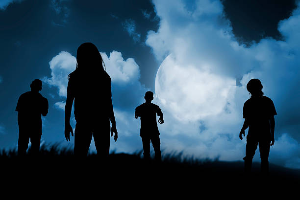 group of zombie walking at night - zombie apocalypse stock photos and pictures