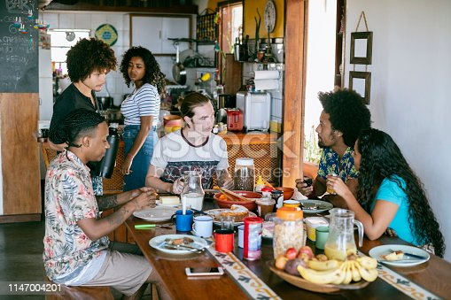 Candid view of Brazilian friends sitting around table with people in kitchen preparing food and drink, backpackers, gap year students
