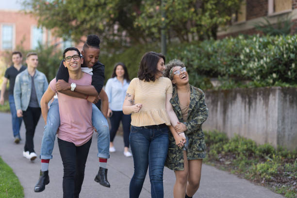 Group photo of college students on campus sidewalk together A multi-racial group of university students cheerfully walk down a sidewalk together. One student is carrying his boyfriend on his back. lgbtqi rights stock pictures, royalty-free photos & images