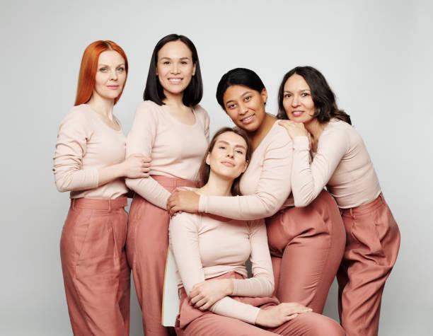Gruppenfoto von verschiedenen attraktiven echten Damen mit verschiedenen Skins posiert zusammen vor isoliertem Hintergrund – Foto