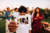 Woman showing picture in front with friends partying in background. Group photo of party people.