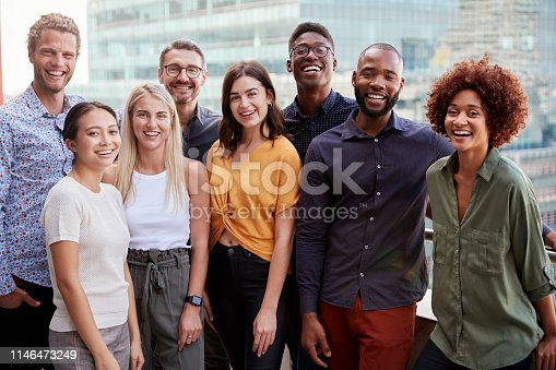 Group portrait of a creative business team standing outdoors, three quarter length, close up