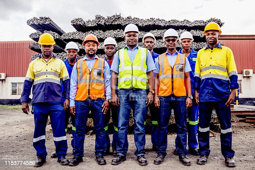 Africa, Industry, Business, Steel Factory, People - Portrait of a Factory Manual Worker, Supervisor, Safety Officer and Factory Manager Standing In front of the Steel Bar Storage Yard.