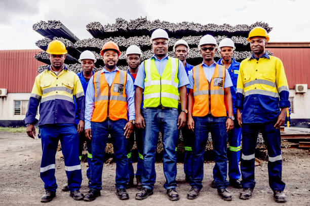 Group Portrait of Confident African Steel Factory Worker Team in Africa Africa, Industry, Business, Steel Factory, People - Portrait of a Factory Manual Worker, Supervisor, Safety Officer and Factory Manager Standing In front of the Steel Bar Storage Yard. labor union stock pictures, royalty-free photos & images