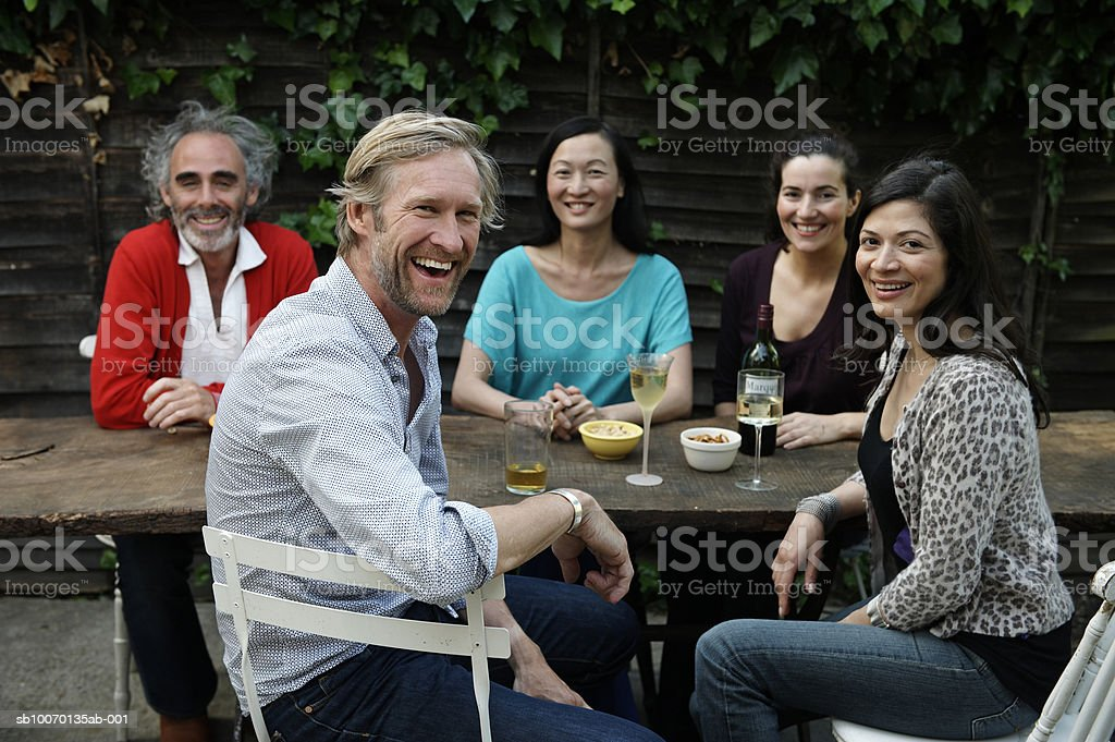 Group portrait of five friends sitting at table in garden royalty-free stock photo