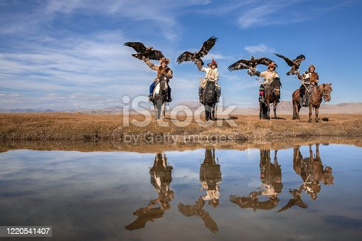 Group portrait of four traditional kazakh eagle hunters with their golden eagles reflecting in the river water. Ulgii, Western Mongolia.